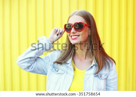 Portrait pretty young smiling woman in red sunglasses over colorful yellow background - stock photo