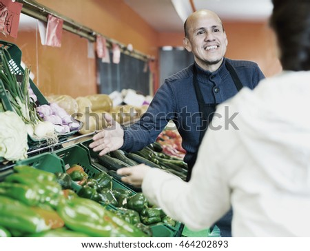 Portrait professional worker selling vegetables to female young customer