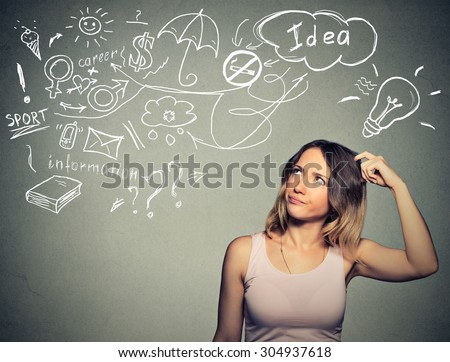 Portrait puzzled young woman thinking scratching head has many ideas looking up isolated gray wall background. Human face expression emotion feeling life perception. Decision making process concept - stock photo
