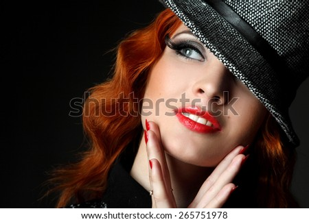Portrait redhead, a young woman in hat. against a dark background. sexy look, lush red lips. fashion evening make-up. artistic hand gestures - stock photo