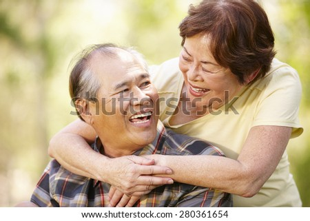 Portrait romantic senior Asian couple outdoors - stock photo