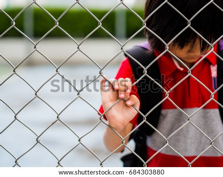 Portrait sad boy behind fence mesh netting. Emotions concept - sadness, sorrow, melancholy.