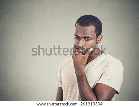 Portrait sad, depressed, worried young man looking down isolated on grey wall background. Human face expressions, emotion, feelings, reaction, life perception - stock photo