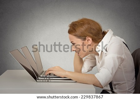 Portrait sad exhausted stressed young woman working on several computers sitting at her office desk isolated on grey wall background. Negative human emotion face expression. Long working hours