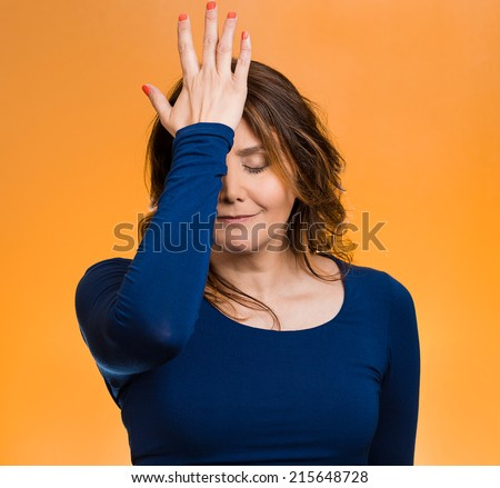 Portrait sad middle aged woman realizes mistake, regrets, slapping hand on head to say duh, isolated orange background. Negative emotions, facial expression, feelings, body language, reaction - stock photo