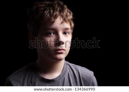 Portrait sad teenage boy on a black background - stock photo