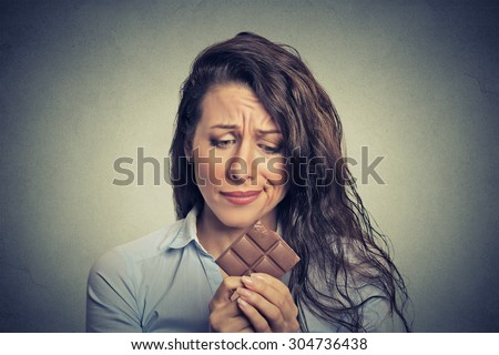 Portrait sad young woman tired of diet restrictions craving sweets chocolate isolated on gray wall background. Human face expression emotion. Nutrition concept. Feelings of guilt  - stock photo