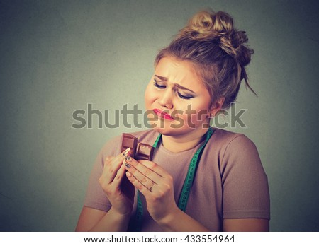 Portrait sad young woman with measuring tape tired of diet restrictions craving sweets chocolate isolated on gray wall background. Human face expression emotion. Nutrition concept. Feeling of guilt - stock photo