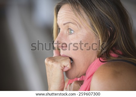 Portrait scared mature woman, fearful, shocked stressed, worried facial expression, nail biting, hand between teeth, blurred background, copy space. - stock photo