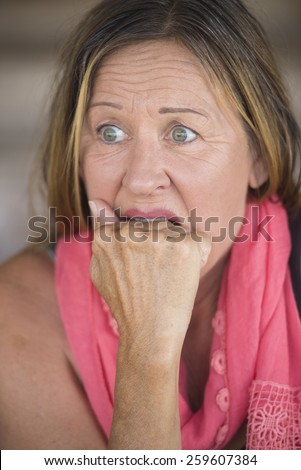 Portrait scared mature woman, fearful, shocked stressed, worried facial expression, nail biting, hand between teeth, blurred background. - stock photo