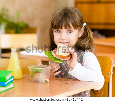 portrait schoolgirl looking at camera while having lunch during - stock photo
