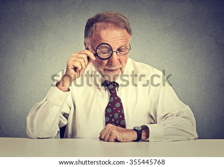 Portrait senior business man looking through a magnifying glass sitting at office desk