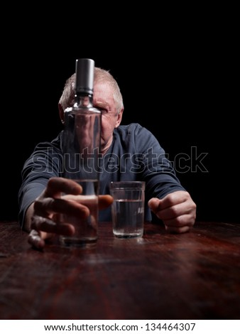portrait senior man  pouring white alcohol in a glass
