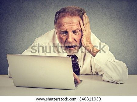 Portrait senior stressed man working on laptop sitting at table isolated on gray wall background  - stock photo