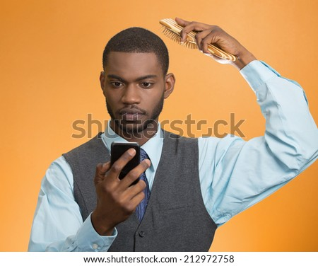 Portrait serious, worried business man, corporate executive reading bad news on smart phone holding mobile, combing his hair isolated orange background. Human face expression, emotion, phone addiction - stock photo