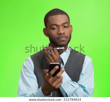 Portrait serious young business man shaving his face, using trimmer texting, reading news on smart phone isolated green background. Human face expression busy life of corporate executive. Multitasking - stock photo