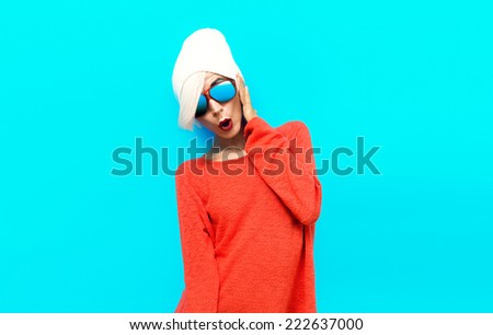 Portrait Sexy Blond Model in red sweater on blue background. Studio Fashion Photo - stock photo