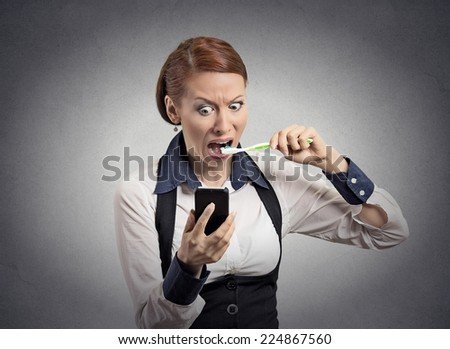 Portrait shocked corporate business woman reading news e-mail on smart phone brushing teeth with toothbrush isolated grey wall office background. Human face expression emotion. Phone addiction concept - stock photo
