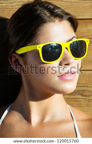 Portrait shot of a beautiful woman in a park with sunglasses
