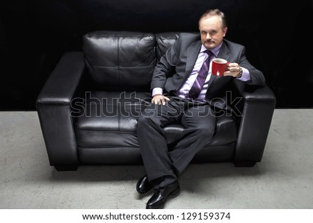 Portrait shot of a gangster in full suit sitting on couch with coffee cup