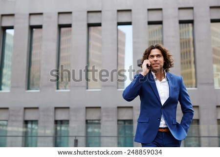 Portrait shot of a handsome business man talking on his mobile phone while walking in city - stock photo