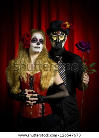 Portrait shot of a scary man holding a flower while woman wearing sugar skull standing with hand clasped.