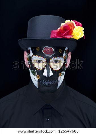 Portrait shot of a scary man wearing traditional sugar skull make-up and hat decorated with roses over plain black background.
