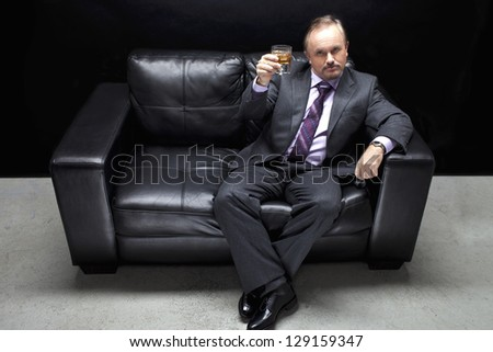 Portrait shot of a well dressed gangster sitting on black couch with a glass of whiskey