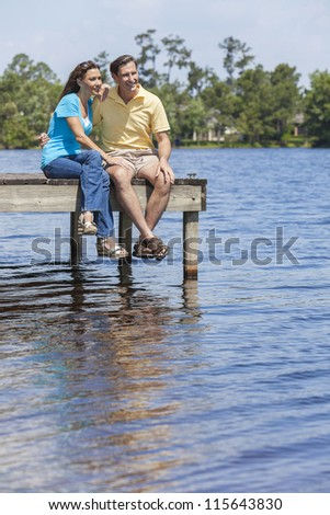 Portrait shot of an attractive, successful and happy middle aged man and woman couple in their thirties, sitting together on a jetty or pier by a lake - stock photo