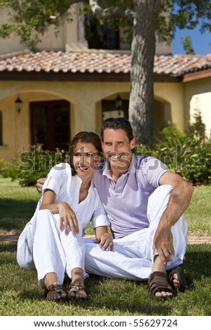 Portrait shot of an attractive, successful and happy middle aged man and woman couple in their thirties, sitting together outside under a tree and smiling. - stock photo