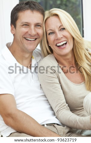 Portrait shot of an attractive, successful and happy middle aged man and woman couple in their forties, sitting together at home on a sofa, smiling and laughing - stock photo