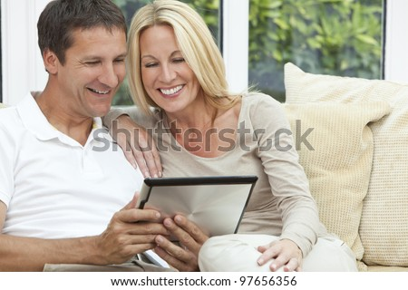 Portrait shot of an attractive, successful and happy middle aged man and woman couple in their forties, sitting together at home on a sofa using tablet computer - stock photo