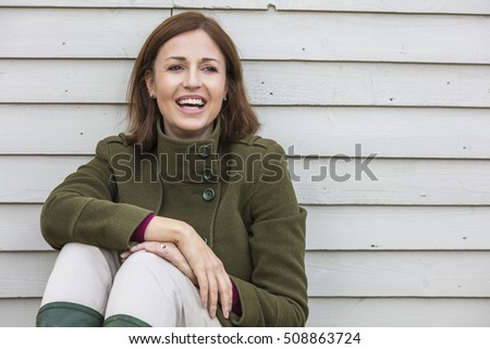 Portrait shot of an attractive, successful and happy middle aged woman female outside laughing