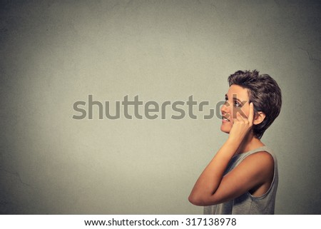 Portrait side profile happy woman thinking looking up finger on head isolated on grey wall background with copy space. Human face expressions, emotions, feelings, body language, perception