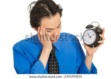 Portrait sleeping young man holding alarm clock isolated on white background. Long working hours, lack of sleep, sleep deprivation, no motivation concept. Face expression - stock photo