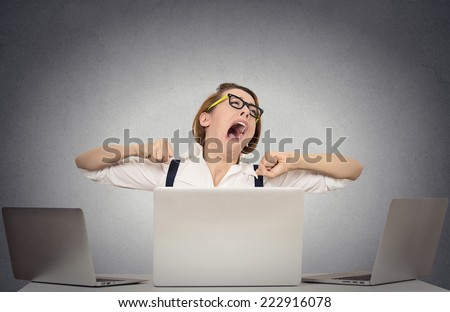 Portrait sleepy yawning business woman with wide open mouth eyes closed looking bored sitting at desk with computers isolated office grey wall background. Emotions face expression. Long working hours - stock photo