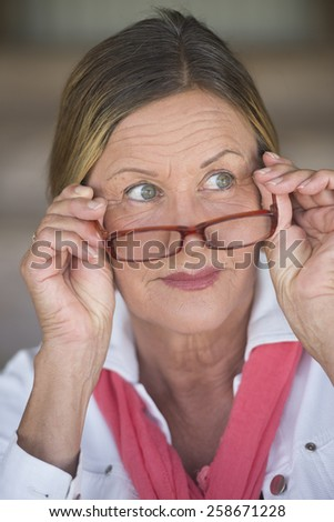 Portrait smart attractive mature business woman with glasses and curious interested expression, blurred background. - stock photo
