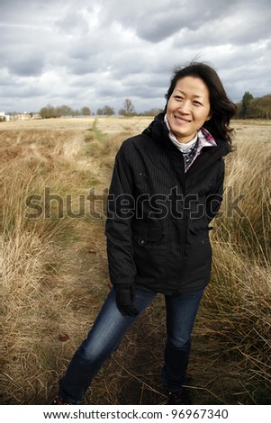 Portrait smiling asian woman, looking off into distance in the field