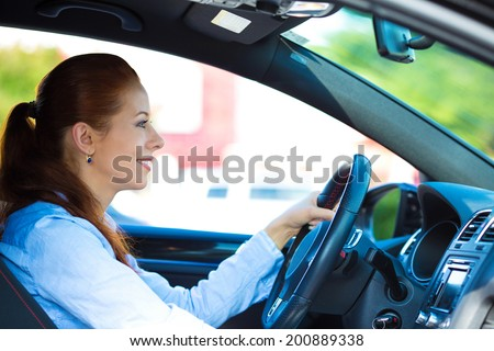 Portrait smiling, attractive brunette woman, buckled up, driving, testing her new black car, automobile, purchased at dealership, isolated street, city traffic background. Safe driving habits concept