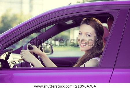 Portrait smiling, attractive happy woman, buckled up, driving, testing her new violet car, automobile, purchased at dealership, isolated street, city traffic background. Safe driving habits concept - stock photo