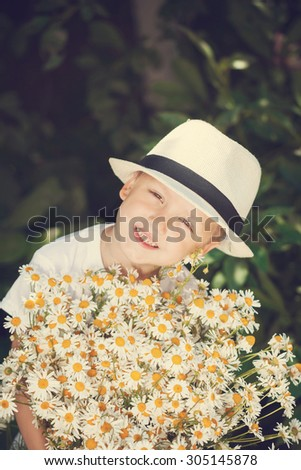 Portrait smiling boy in a hat with big white bouquet of chamomiles. Summertime. Toning image - stock photo