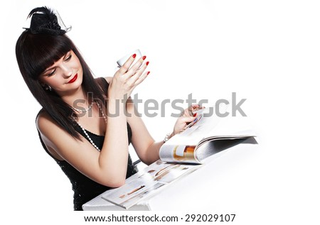 Portrait smiling brunette with red lipstick and white pearls, reading magazine, drink tea
