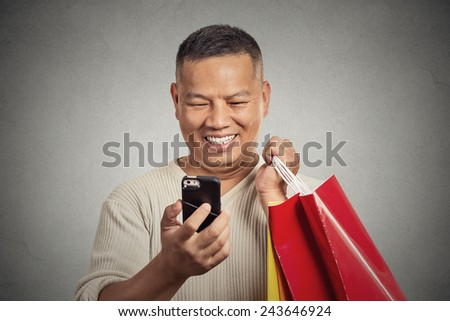 Portrait smiling handsome man holding red shopping bags looking at his smartphone isolated on grey wall background  - stock photo