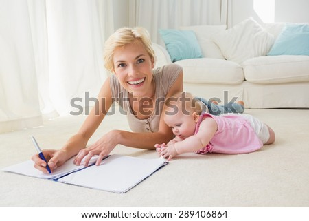 Portrait smiling mother with her baby girl writting on a copybook at home in the living room - stock photo
