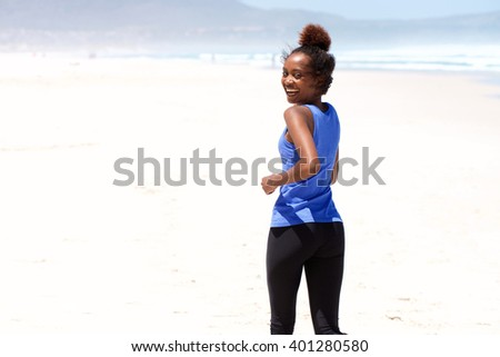Portrait smiling young african woman jogging on the beach and looking back