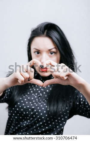 Portrait smiling young woman making heart sign with hands