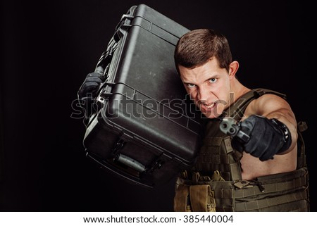 Portrait soldier or private military contractor aiming with a pistol and holding a box. war, army, weapon, technology and people concept. Image on a black background. - stock photo