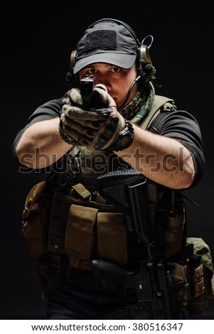 Portrait  soldier or private military contractor holding black gun. war, army, weapon, technology and people concept. Image on a black background.