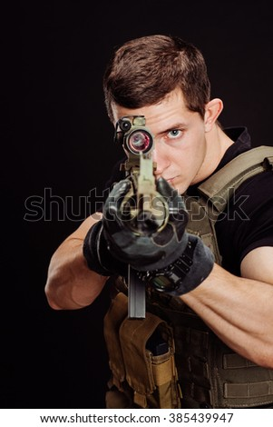 Portrait soldier or private military contractor holding sniper rifle and aiming. war, army and people concept. Image on a black background.