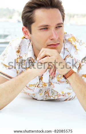 Portrait sporty handsome young businessman resting on a white yacht in the sea